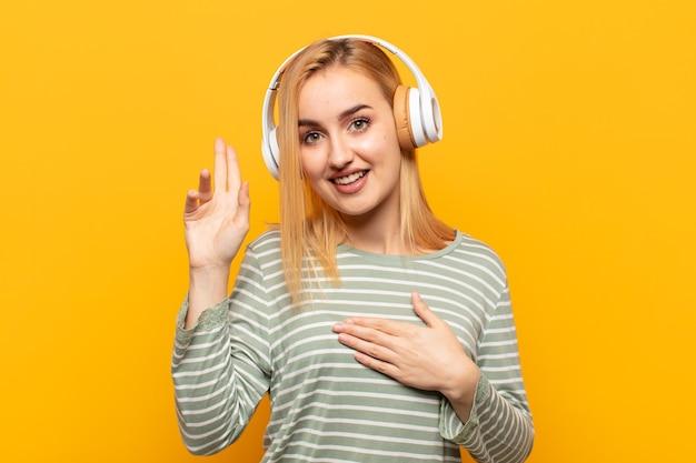 Giovane donna bionda che sembra felice, sicura di sé e degna di fiducia, sorridente e che mostra il segno della vittoria