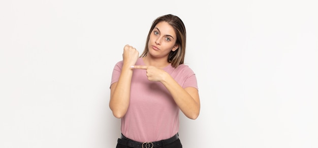 La giovane donna bionda che sembra impaziente e arrabbiata, indica l'orologio, chiede puntualità, vuole essere puntuale
