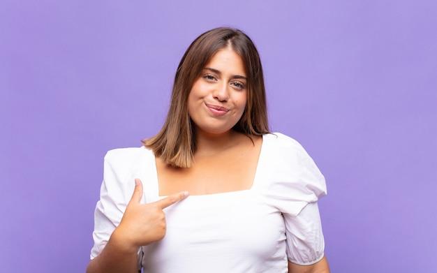 Giovane donna bionda che sembra orgogliosa, sicura e felice, sorridente e indicando se stessa o facendo il segno numero uno