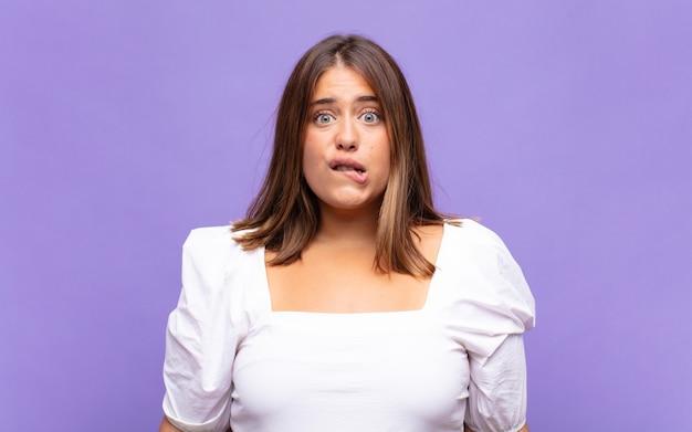 Giovane donna bionda che sembra perplessa e confusa, mordendosi il labbro con un gesto nervoso, non conoscendo la risposta al problema