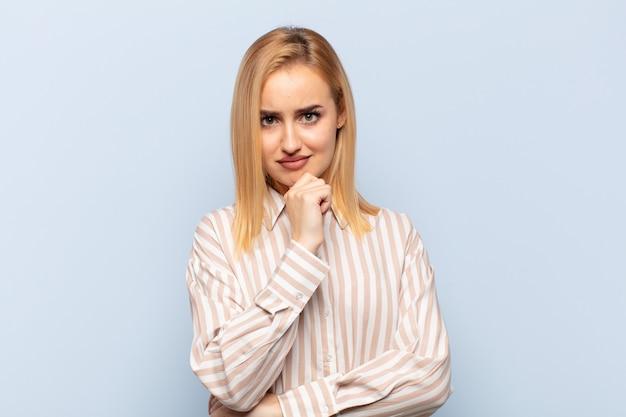 Giovane donna bionda che sembra seria, confusa, incerta e premurosa, dubitando tra le opzioni o le scelte
