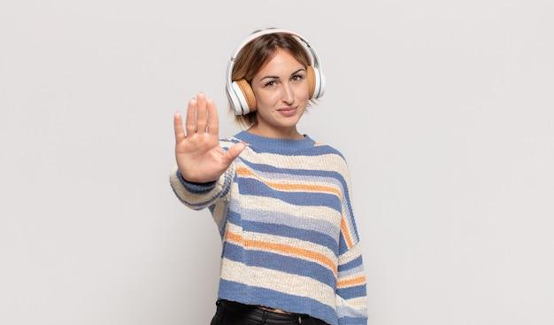 Giovane donna bionda che sembra serio, severo, dispiaciuto e arrabbiato che mostra il palmo aperto che fa il gesto di arresto