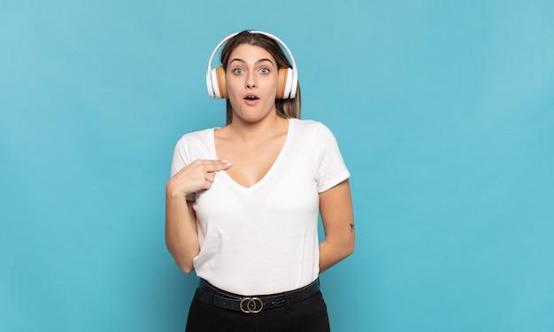 Giovane donna bionda che sembra scioccata e sorpresa con la bocca spalancata, indicando se stesso