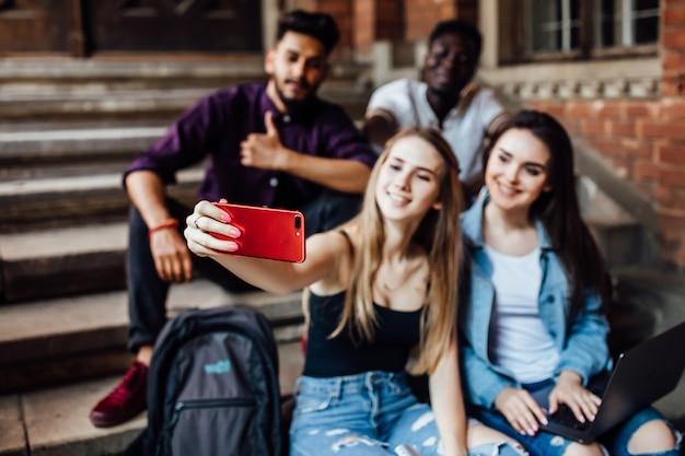 Giovane donna bionda che fa selfie con i suoi amici studenti in universit
