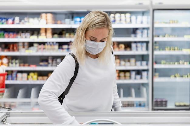 Una giovane donna bionda in una mascherina medica sceglie cibi congelati in un grande supermercato. alimentazione sana e vegetarismo. pandemia di coronavirus.