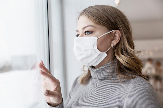 Giovane donna bionda in una maschera medica guarda fuori dalla finestra. solitudine in isolamento. pandemia di coronavirus.