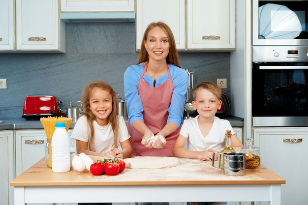 Giovane donna bionda, madre e figli che si divertono durante la cottura della pasta