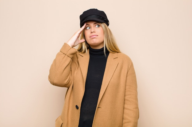 Giovane donna bionda in preda al panico per una scadenza dimenticata, sentirsi stressata, dover nascondere un disordine o un errore sul muro