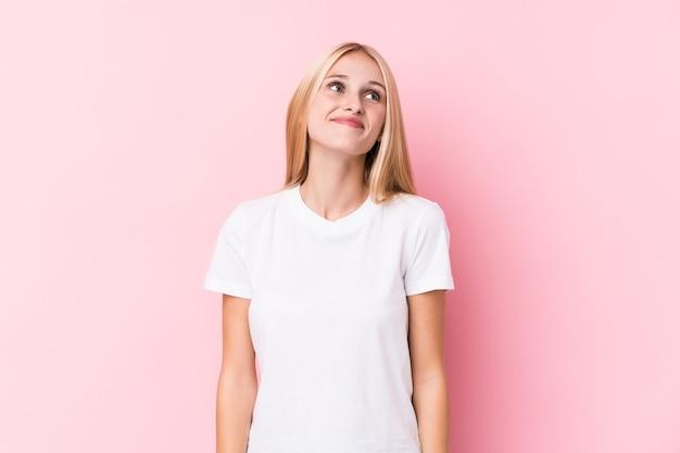 Giovane donna bionda su sfondo rosa, sognando di raggiungere obiettivi e scopi
