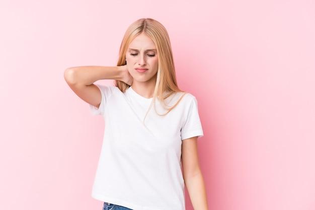 Giovane donna bionda in rosa soffre di dolore al collo a causa di uno stile di vita sedentario.