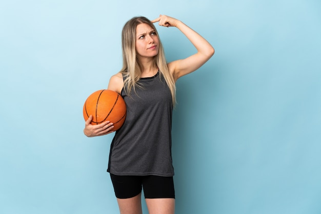 Giovane donna bionda che gioca pallacanestro isolata sulla parete blu che ha dubbi e con l'espressione confusa del fronte