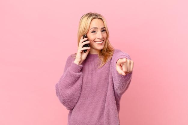Giovane donna bionda che punta alla telecamera scegliendo te e parlando con uno smartphone