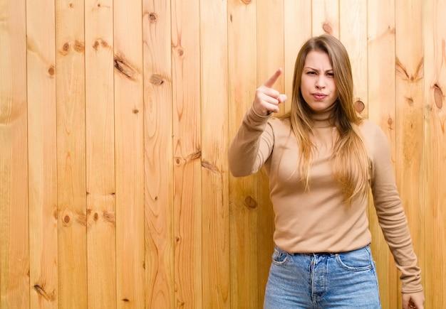 Giovane donna bionda che indica con un'espressione aggressiva arrabbiata che sembra un capo furioso e pazzo