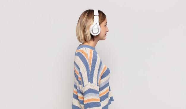 Giovane donna bionda sulla vista di profilo che cerca di copiare lo spazio davanti, pensare, immaginare o sognare ad occhi aperti