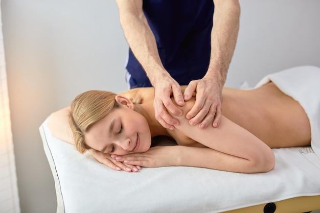 Giovane donna bionda che riceve massaggio alla schiena dal massaggiatore maschio ritagliato nel centro termale, rilassata signora caucasica che si gode le procedure termali da professionisti, sdraiata sul letto a torso nudo. ritratto vista laterale