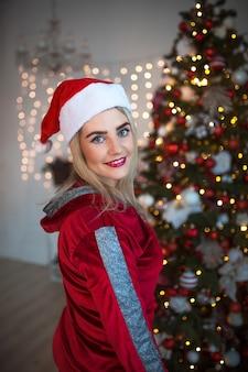 Giovane donna bionda in una tuta rossa sulle decorazioni natalizie