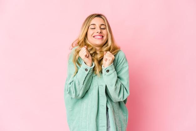 Giovane donna bionda che grida, molto eccitata, appassionata, soddisfatta di qualcosa