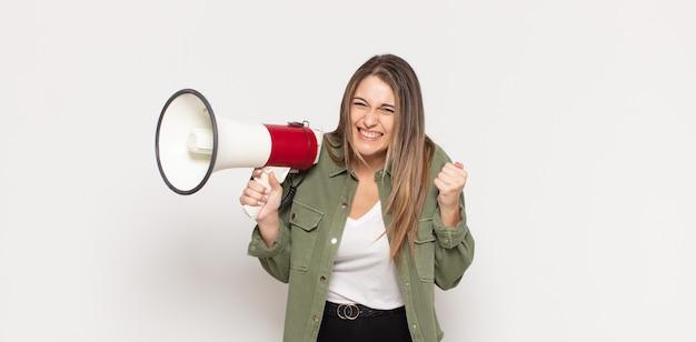 Giovane donna bionda che grida in modo aggressivo con un'espressione arrabbiata o con i pugni chiusi per celebrare il successo