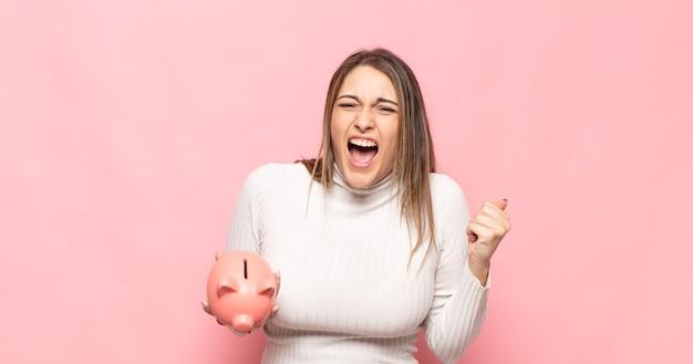 Giovane donna bionda che grida in modo aggressivo con un'espressione arrabbiata o con i pugni serrati per celebrare il successo