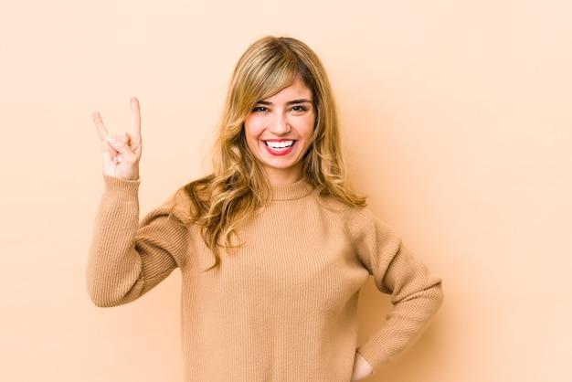 Giovane donna bionda che mostra un gesto di corna come un concetto di rivoluzione
