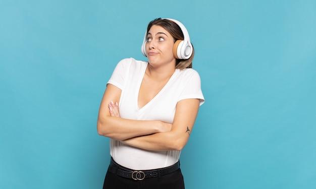 Giovane donna bionda che scrolla le spalle, sentendosi confusa e incerta, dubbiosa con le braccia incrociate e lo sguardo perplesso