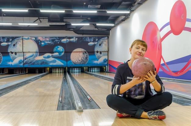 Giovane donna bionda seduta sul pavimento in bowling club è in possesso di palla da bowling