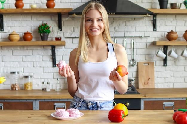Sorrisi di giovane donna bionda, donna in cucina sceglie tra dolci e frutta, cibo sano