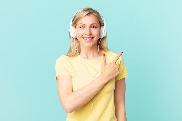 Giovane donna bionda che sorride allegramente, si sente felice e indica il lato e ascolta musica.