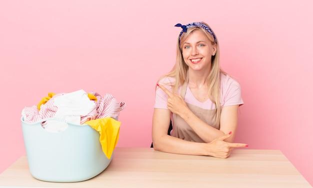 Giovane donna bionda che sorride allegramente, si sente felice e indica il lato. lavare i vestiti concetto clothes