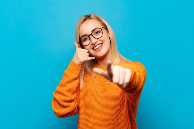 Giovane donna bionda che sorride allegramente e indica la telecamera mentre fa una chiamata dopo un gesto, parlando al telefono