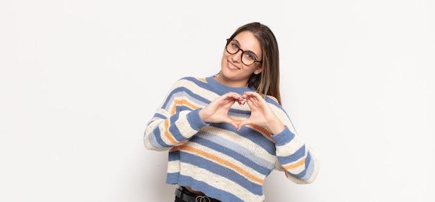 Giovane donna bionda che sorride e si sente felice, carina, romantica e innamorata, facendo forma di cuore con entrambe le mani