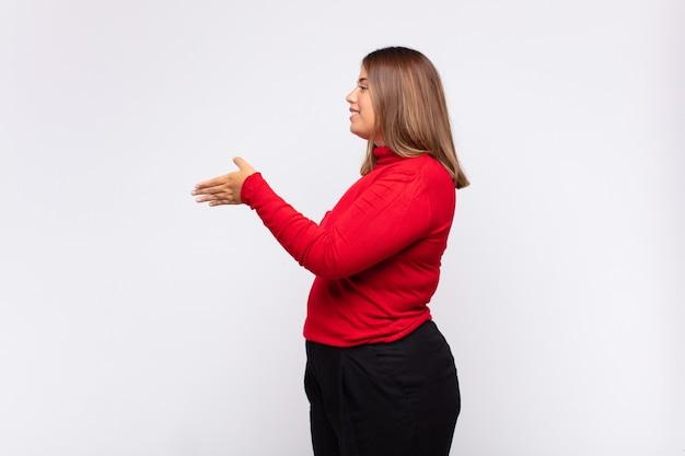 Giovane donna bionda sorridente, salutandoti e offrendoti una stretta di mano per chiudere un affare di successo, concetto di cooperazione