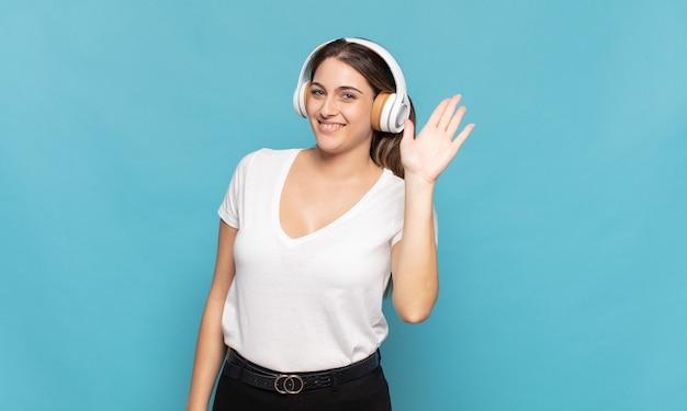 Giovane donna bionda che sorride allegramente e allegramente, agitando la mano, dandoti il benvenuto e salutandoti o salutandoti