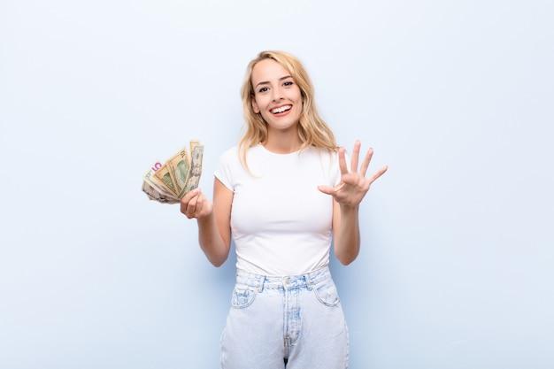 Giovane donna bionda sorridente e guardando amichevole, mostrando il numero cinque o quinto con la mano in avanti, conto alla rovescia con banconote in dollari