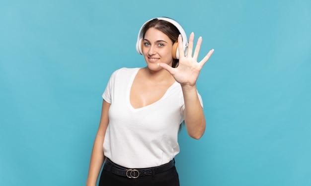 Giovane donna bionda sorridente e dall'aspetto amichevole, mostrando il numero cinque o il quinto con la mano in avanti, conto alla rovescia