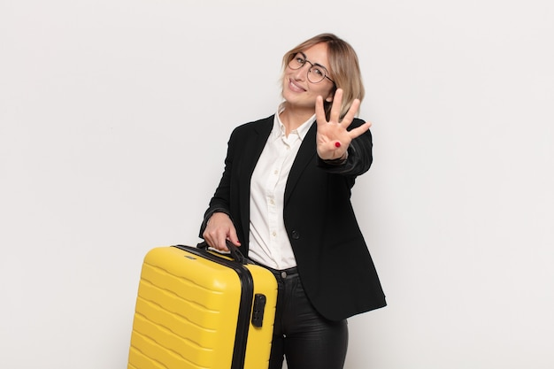 Giovane donna bionda che sorride e sembra amichevole, mostrando il numero quattro o quarto con la mano in avanti, conto alla rovescia