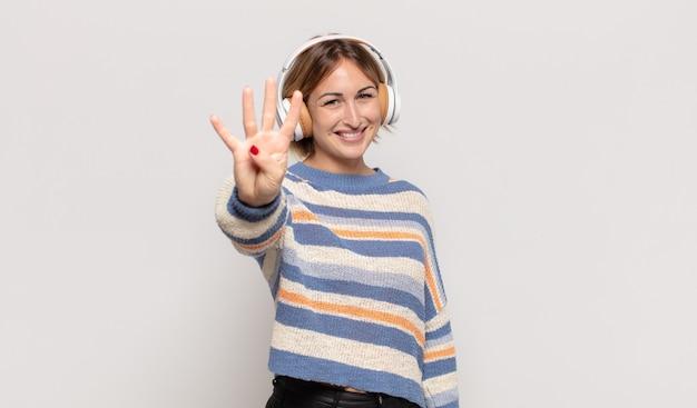 Giovane donna bionda che sorride e sembra amichevole, mostrando il numero quattro o il quarto con la mano in avanti, conto alla rovescia