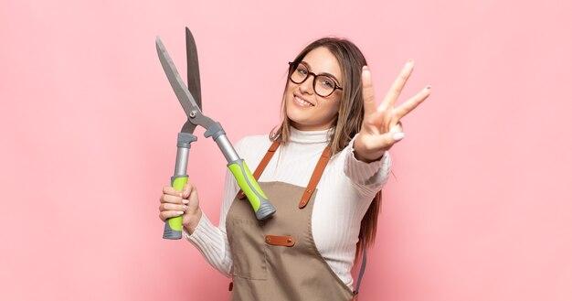 Giovane donna bionda sorridente e guardando amichevole, mostrando il numero tre o terzo con la mano in avanti, conto alla rovescia