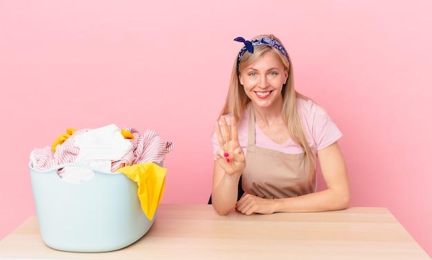 Giovane donna bionda sorridente e dall'aspetto amichevole, mostrando il numero tre. lavare i vestiti concetto