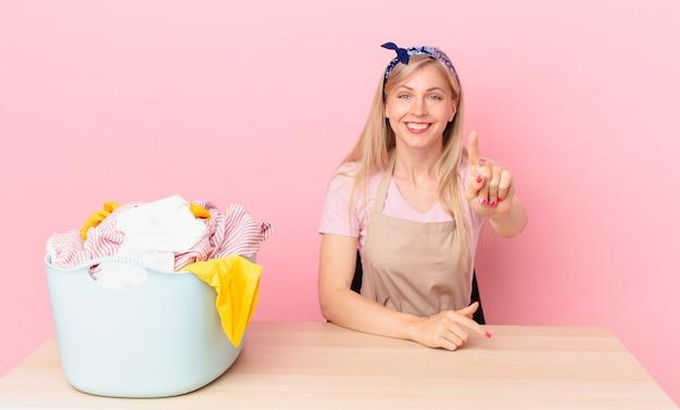Giovane donna bionda che sorride con orgoglio e sicurezza facendo il numero uno. lavare i vestiti concetto