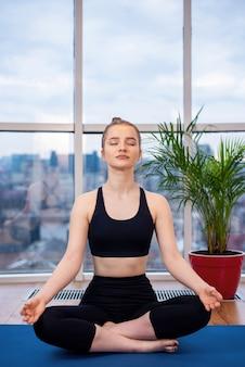 Giovane donna bionda in abiti sportivi sta meditando su una stuoia di yoga con gli occhi chiusi