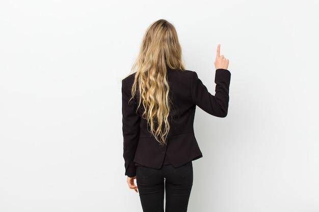 Giovane donna bionda che sta e che indica l'oggetto, retrovisione sopra la parete bianca
