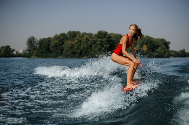 Giovane surfista biondo della donna che guida giù l'onda di spruzzatura blu
