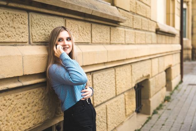 Giovane donna bionda che cattura dal telefono cellulare sulla strada