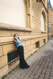 Giovane donna bionda che cattura dal telefono cellulare in strada