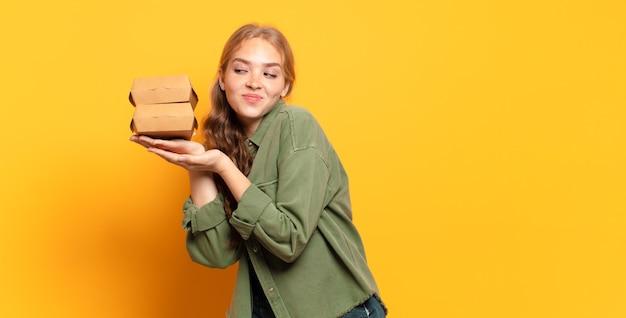 Giovane donna bionda che porta via gli alimenti a rapida preparazione