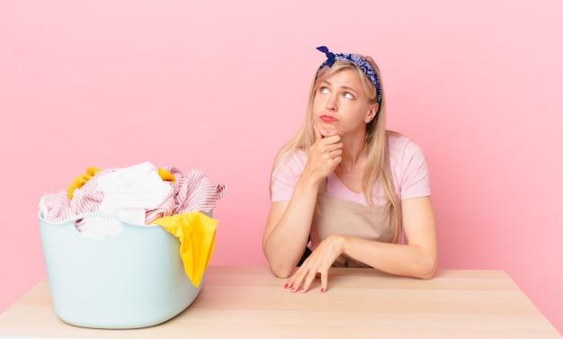 Giovane donna bionda che pensa, si sente dubbiosa e confusa. lavare i vestiti concetto clothes