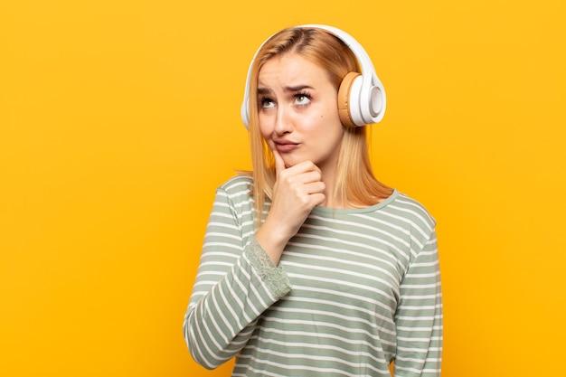 Giovane donna bionda che pensa, si sente dubbiosa e confusa, con diverse opzioni, chiedendosi quale decisione prendere