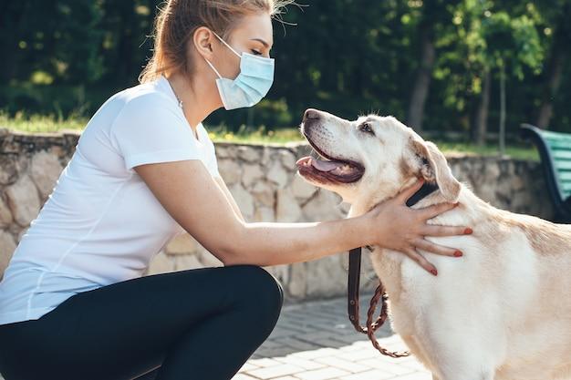 Giovane donna bionda che tocca il suo cane mentre indossa la mascherina medica sul viso e cammina nel parco