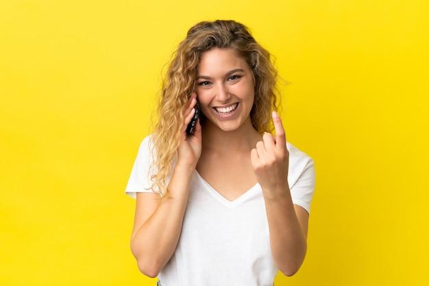 Giovane donna bionda che utilizza il telefono cellulare isolato su sfondo giallo facendo gesto imminente